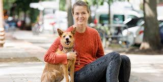 Dogo Founder, Rasa, and her dog, Ūdra, smile for the camera.