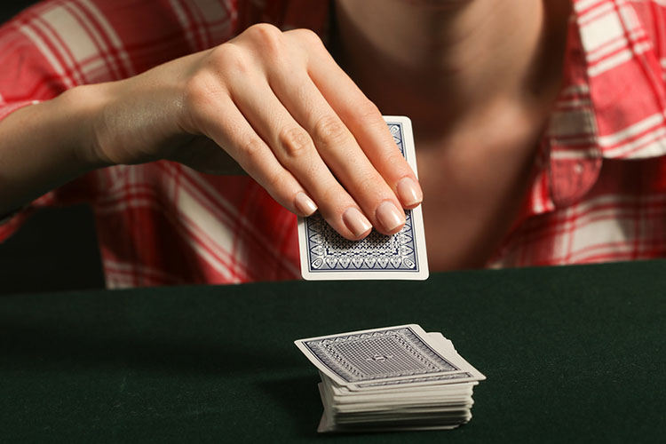 A woman in a plaid shirt playing a 1 player game draws a card from the deck | The Dating Divas