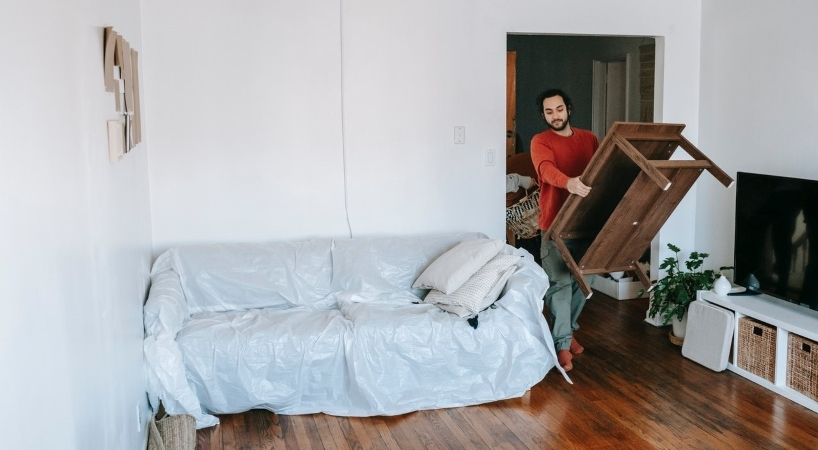 man moving furniture into his apartment