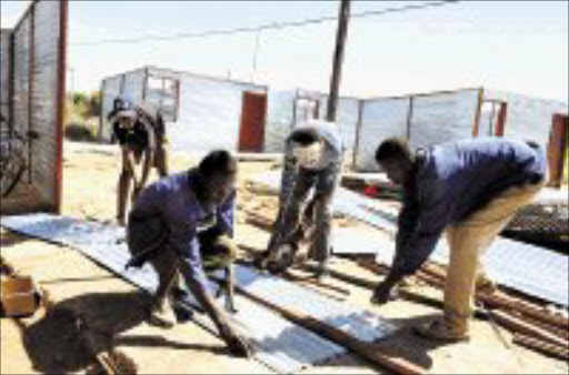 HARD AT WORK: Local workmen hired by the Blouburg municipality in Limpopo are fighting against time to rebuild 67 shacks demolished last year. The Pretoria High Court has ordered the municipality to rebuild them within 14 days. Pic. Elijar Mushiana. 04/2008. © Sowetan.