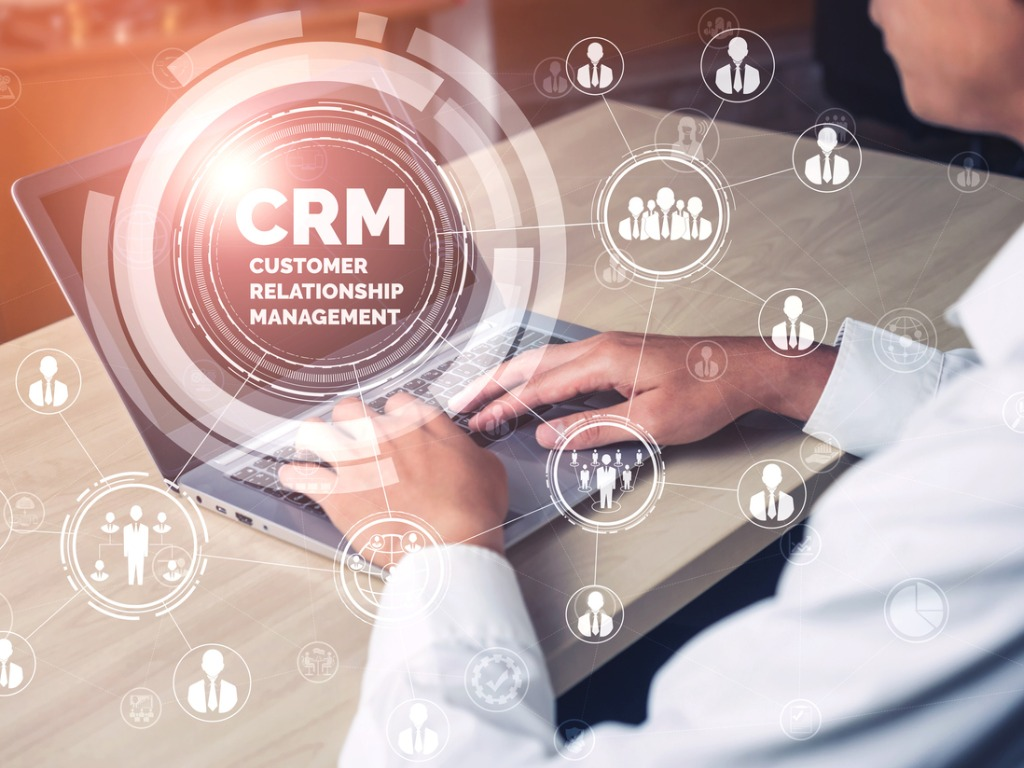 Laptop with hands on it, overlaid with CRM graphic