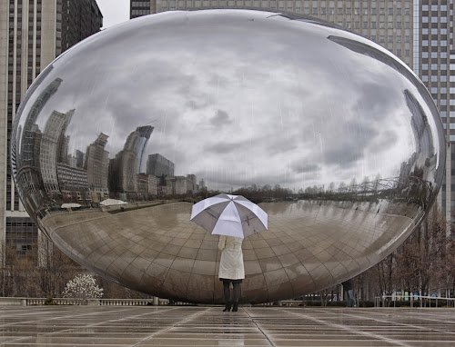 The Bean Lady  by John CHIMON - Travel Locations Landmarks ( skyline, illinois, reflections, travel, the bean, city, raning, weather, cloudy, artist, chicago, wet, place, coat, downtown, rain, shiny, water, clouds, kapoor, bean, umbrella, art, cloud gate, places, steel, anish, sculpture, plates, cloud, lady, stainless, kapur, circle, pwc79 )