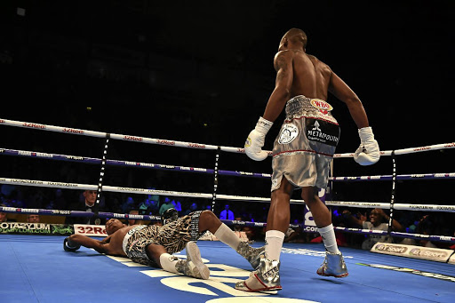 Down and out: World Bantamweight champion Zolani Tete stands over Siboniso Gonya after knocking the challenger out five seconds into their title fight in Belfast to retain his WBO crown. Picture: CHARLES MCQUILLAN/GETTY IMAGES