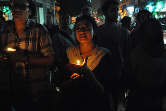 Photo: A woman holds a candle in Talat Harb Square.