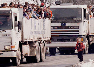 Photo: Bosnian Muslim boy runs by the truck and cries after he fell out of the truck evacuating Muslim refugees out of besieged town of Srebrenica,eastern Bosnia March 31 1993. Bosnian Serb officer Vlada Dakic returned  boy to the truck later.  Photo by Srdjan Ilic / The Associated Press