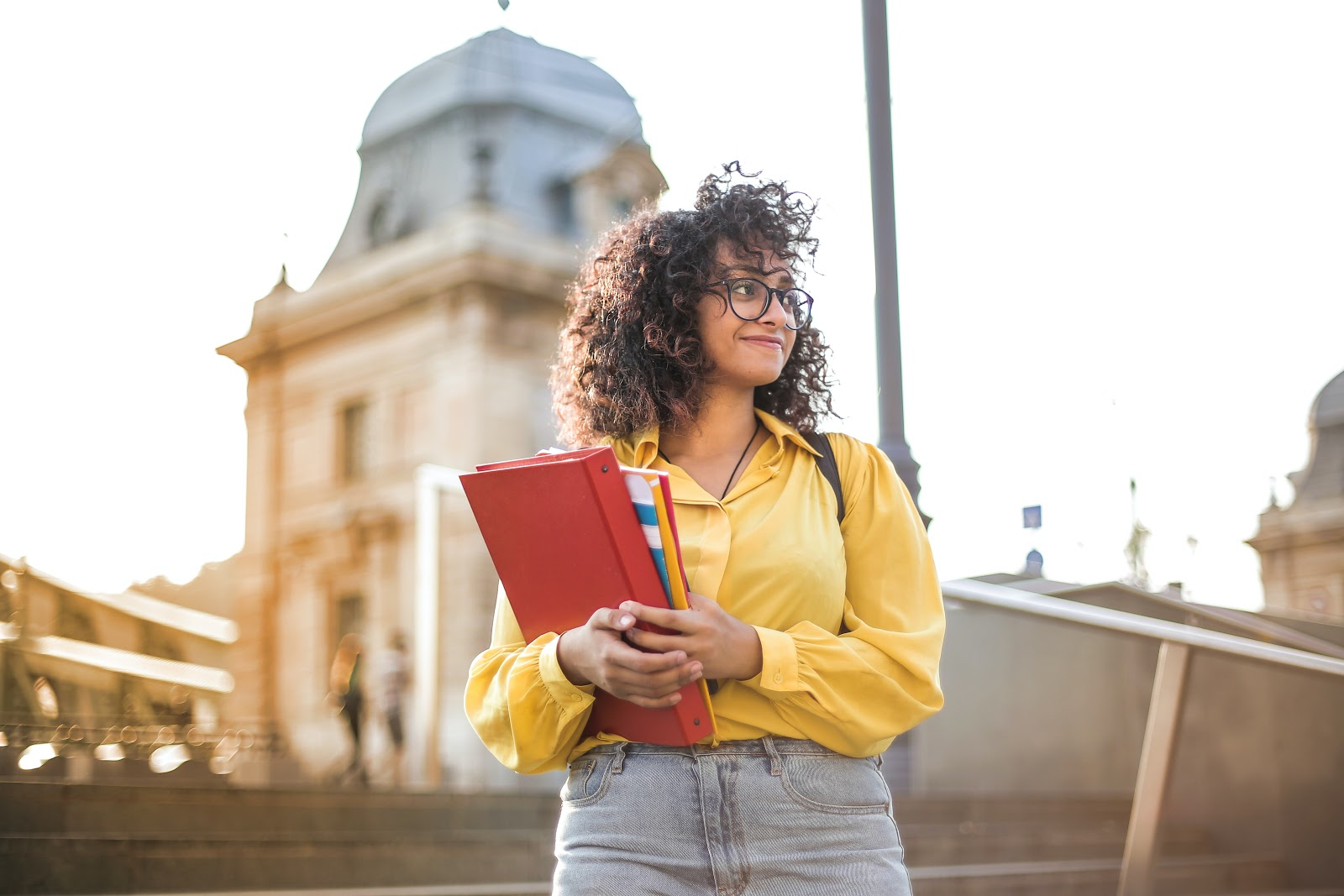 This is a photo of a young college student standing in front of a building on campus with books in her arms.