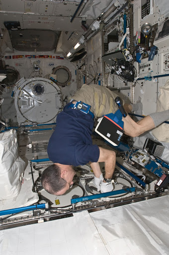 Pettit prepares to insert biological samples in the MELFI-1 in the JPM