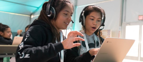 Two children wearing headphones as they engage with a Chromebook