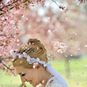 Cherry Blossoms Shower Bride by Kim Wilson - Wedding Bride ( vertical, person, photograph, petals, exterior, veil, people, spring, happy, sunny, lifestyle, flowers, smiling, cherry blossoms, image, bloom, adult, young, bridal, female, wedding, dress, outdoors, woman. 20s, trees, shower, outside )