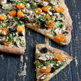 Almond Feta, Mushroom, greens, olives, golden cherry tomatoes. Vegan Mediterranean Pizza with Thin Herbed Spelt Crust. vegan