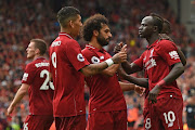 Liverpool's Senegalese striker Sadio Mané (R) celebrates with teammates Roberto Firmino and Mohamed Salah after scoring their third goal during the English Premier League football match between Liverpool and West Ham United at Anfield in Liverpool, north west England on August 12, 2018.