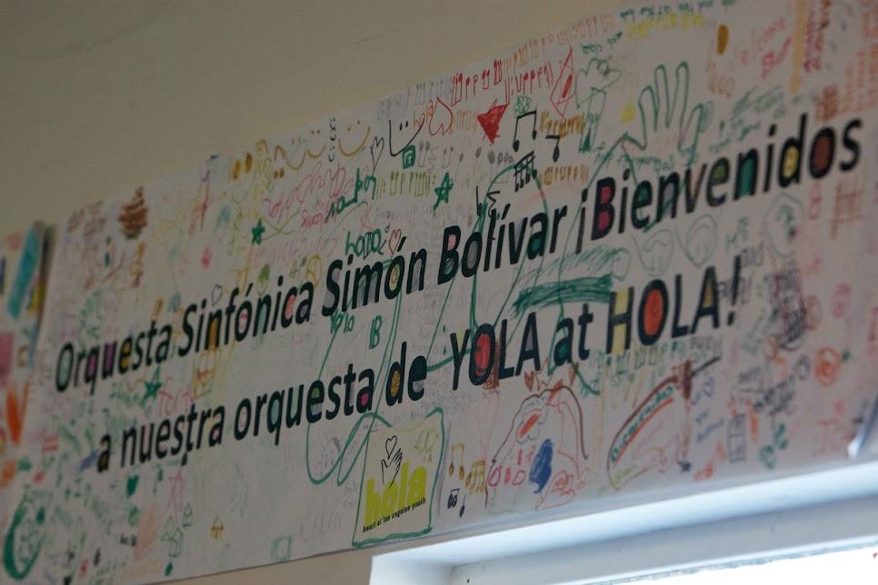 Decenas de integrantes del programa sociocultural angelino YOLA at HOLA, recibieron a los músicos del Cuarteto Francisco de Miranda, el Quinteto Arcadia y el Octeto de Violoncello de la Orquesta Sinfónica Simón Bolívar de Venezuela, con distintas pancartas colocadas en las paredes del salón donde los músicos venezolanos tocaron para los niños de éste proyecto.