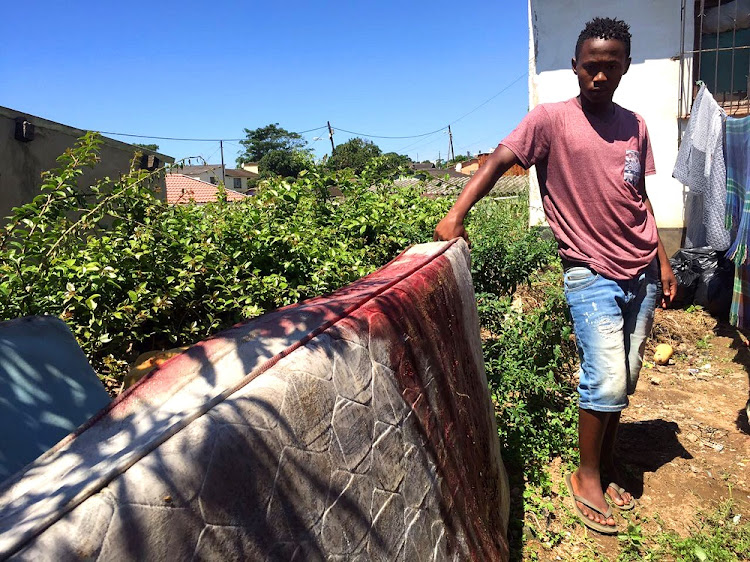 Khulekani Mzila with the mattress on which his brothers had been sleeping when they were shot.
