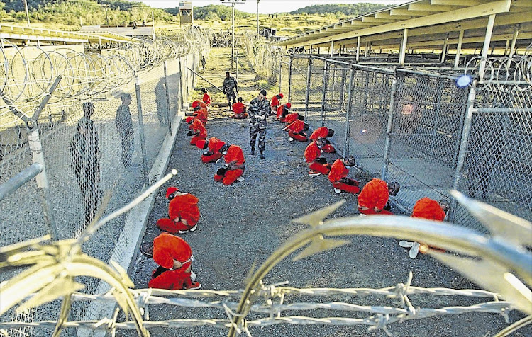 Detainees in jumpsuits kneel in a holding area at Guantánamo Bay in this January 11 2002 photograph taken shortly after the Bush administration opened the prison.