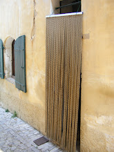 Photo: Séguret door – and our first view of the Provençal curtain door [rideau du porte], which was the solution of how to ventilate a home in the hot Provence summer while keeping out flying insects. They are most traditionally made from short lengths of wood strung closely spaced on thin wires.