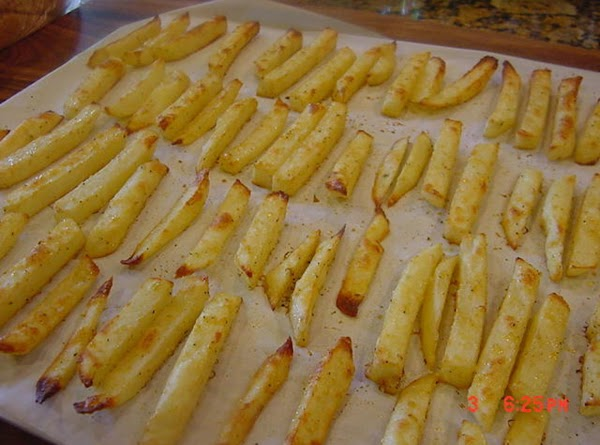 French fries on a baking sheet lined with parchment paper.