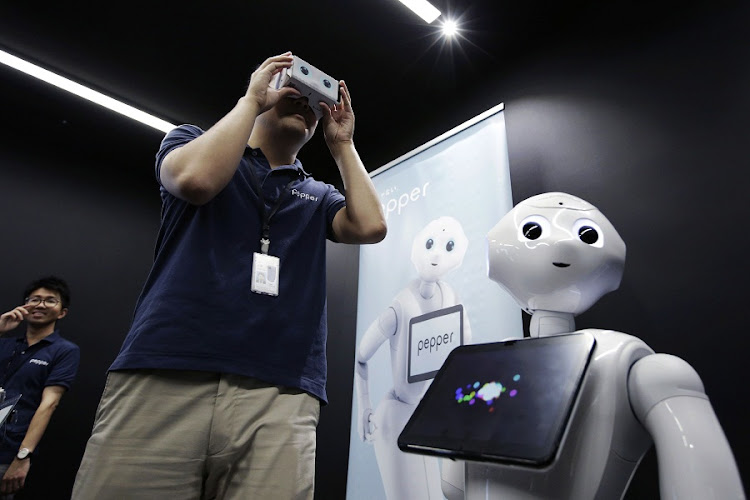 CONTROL: A man uses Google's Cardboard virtual reality headset to communicate with Pepper, a robot made by SoftBank, using Android apps. Picture: BLOOMBERG/KIYOSHI OTA