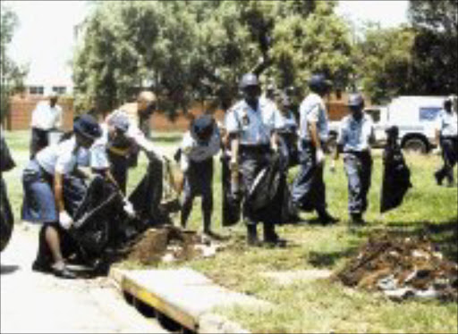 CIVIC DUTY: Police officers pick up litter in the streets of Vereeniging yesterday during a campaign to discourage people from littering. Pic. Len Kumalo. © Sowetan.