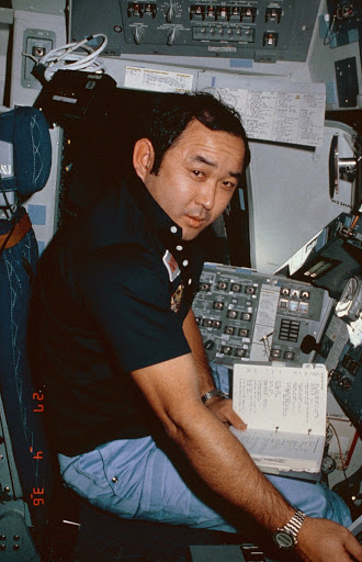 Mission Specialist Ellison Onizuka seated at commander's station