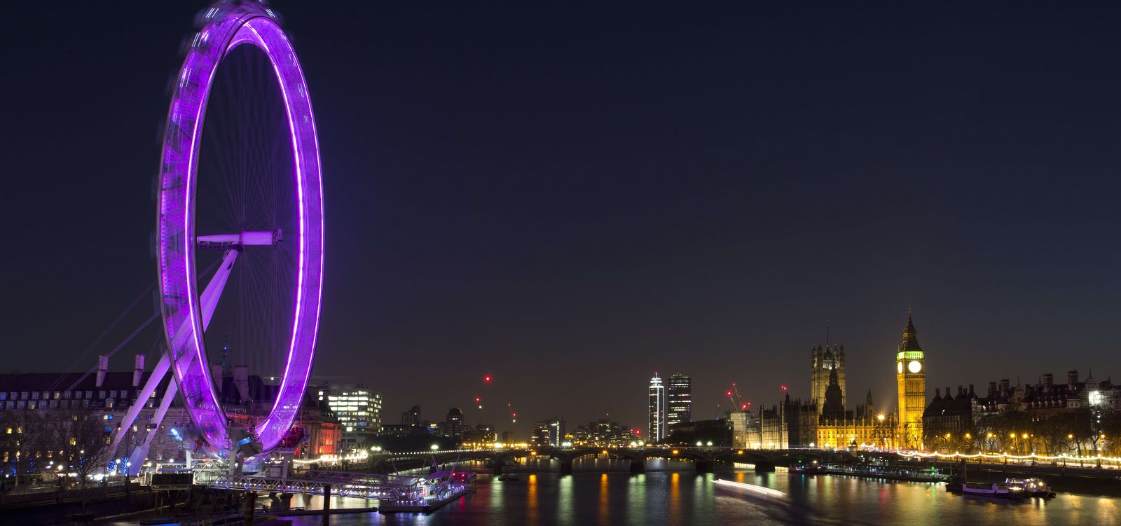 a picture of the london eye next to the thames with the big ben on the opposite side of the river at night