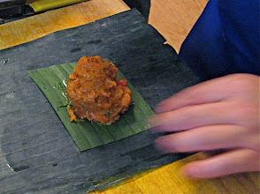 Photo: wrapping curried salmon mixture in banana leaf