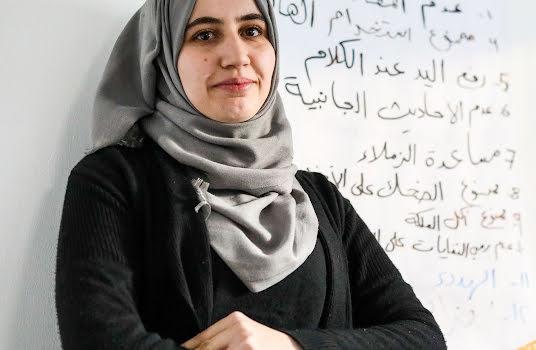 Eine Frau steht vor einem beschriebenen Whiteboard.