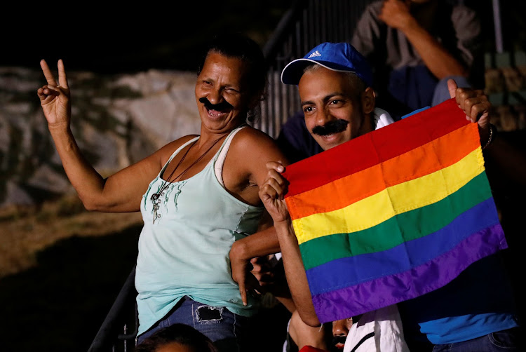 Supporters wear moustaches imitating Venezuela's President Nicolas Maduro while he speaks during a gathering after the results of the election were released, outside of the Miraflores Palace in Caracas.