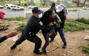 Police grapple with a protester in Kayamandi, Stellenbosch, on Wednesday.