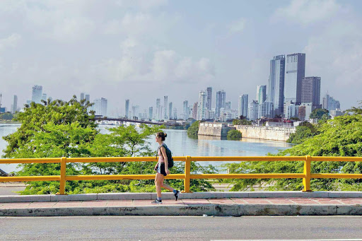 Cartagena-overpass.jpg - A woman strolls across an overpass as the skyline of Cartagena looms in the distance.