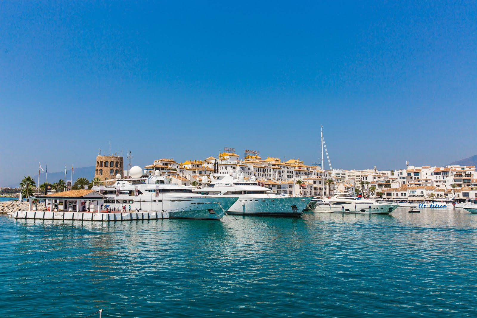 marbella puerto banus port yachts luxury boats on blue sea whitewashed buildings in background costa del sol