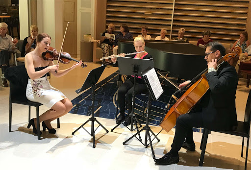 A classical trio performs in the atrium of Viking Sun.