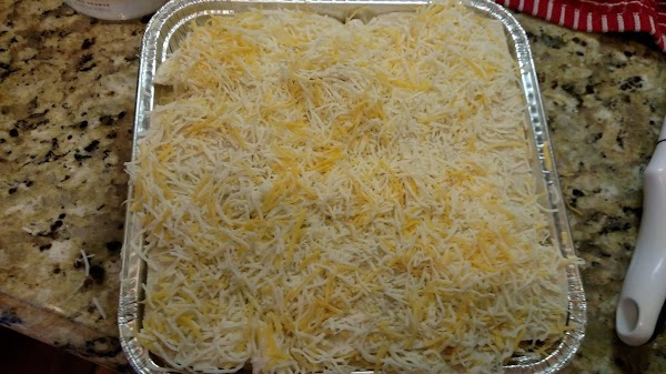 Place enough tortilla pieces to cover the bottom of the baking dish. Cover with...