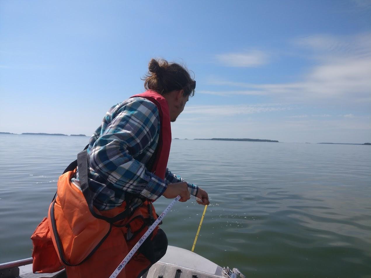 Henkilö laskee sukelluslinjaa veneestä.