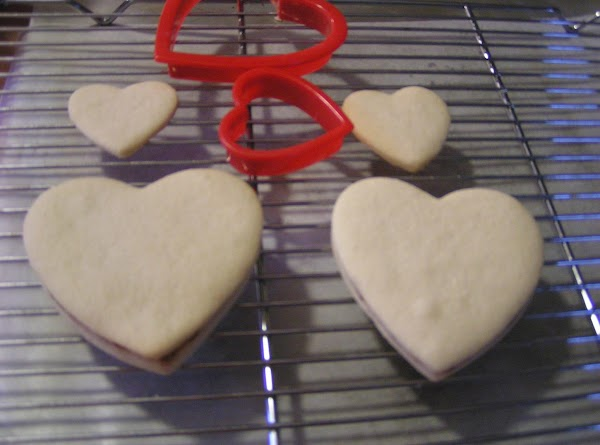 Top with second (large) cookie, pressing backs together with raspberry in center.