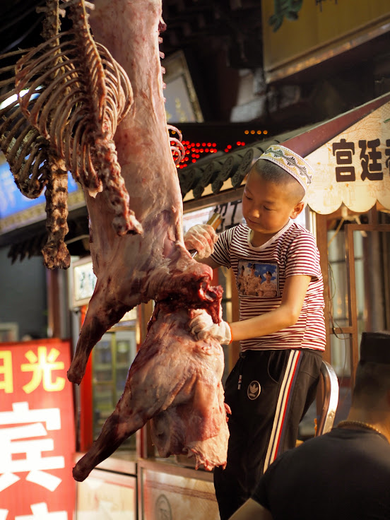 A young butcher in training in Xian Muslim Quarter.