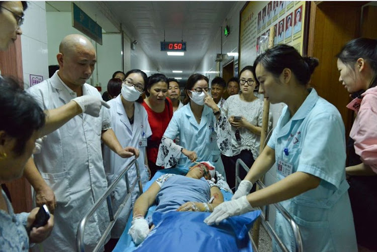 Medical workers treat an injured person on Wednesday, September 12 2018, after a man drove into a crowded public square in Hengdong, China, killing 11 and injuring 44.