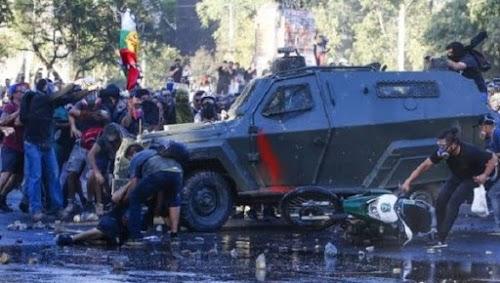 Bürger helfen einem jungen Mann, der am 20.12.2019 in Santiago de Chile von zwei gepanzerten Fahrzeugen überfahren wurde.