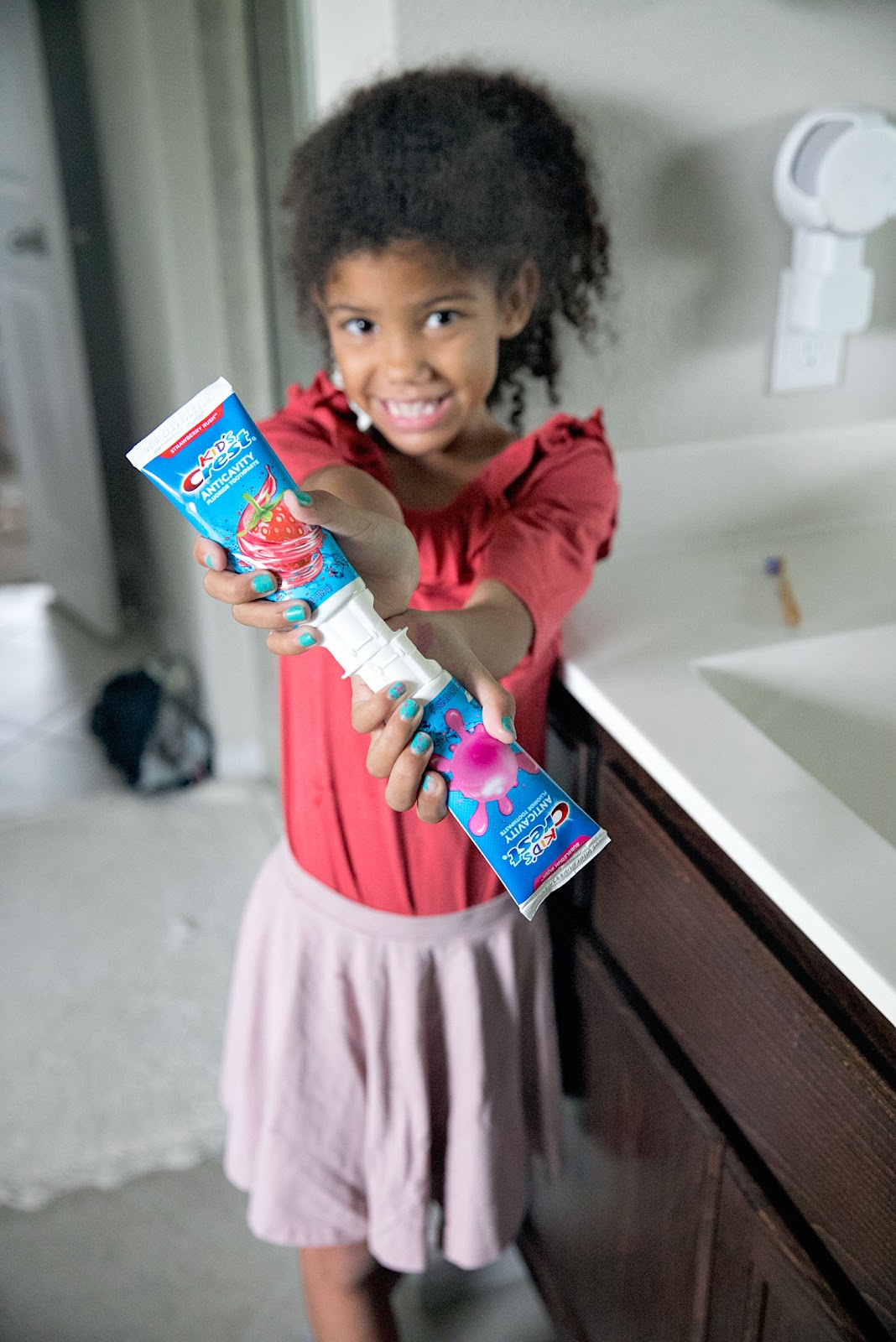 This is our mission to find the best kids toothpaste. Little girl holding strawberry toothpaste and bubblegum toothpaste.
