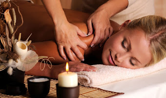 a lady enjoying a swedish massage with candles lying next to the massage bed