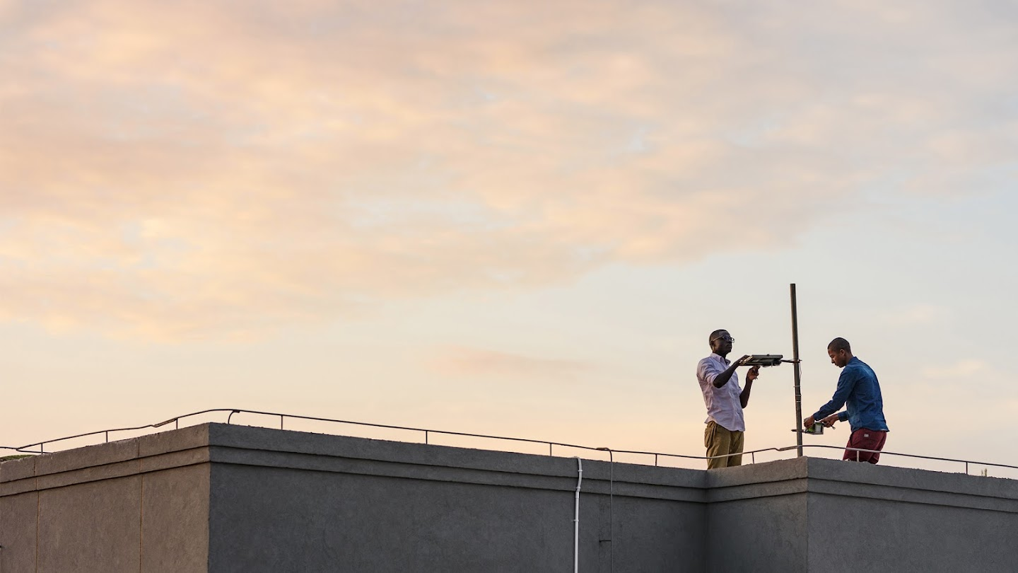 Picture of two men on top of building roof against morning sky setting up pollution measurement devices