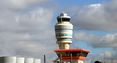 Photo: Airport Control Tower against partly cloudy sky