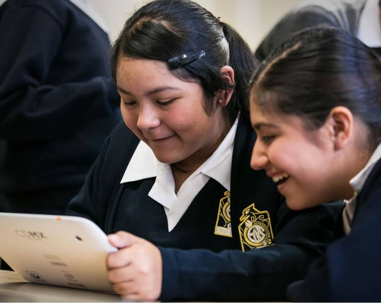 Two girls in school uniform smiling, one of them holding a tablet device