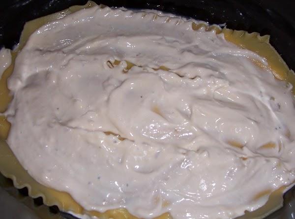 Pour a third of the sauce on bottom of crock pot.  Layer three lasagna...