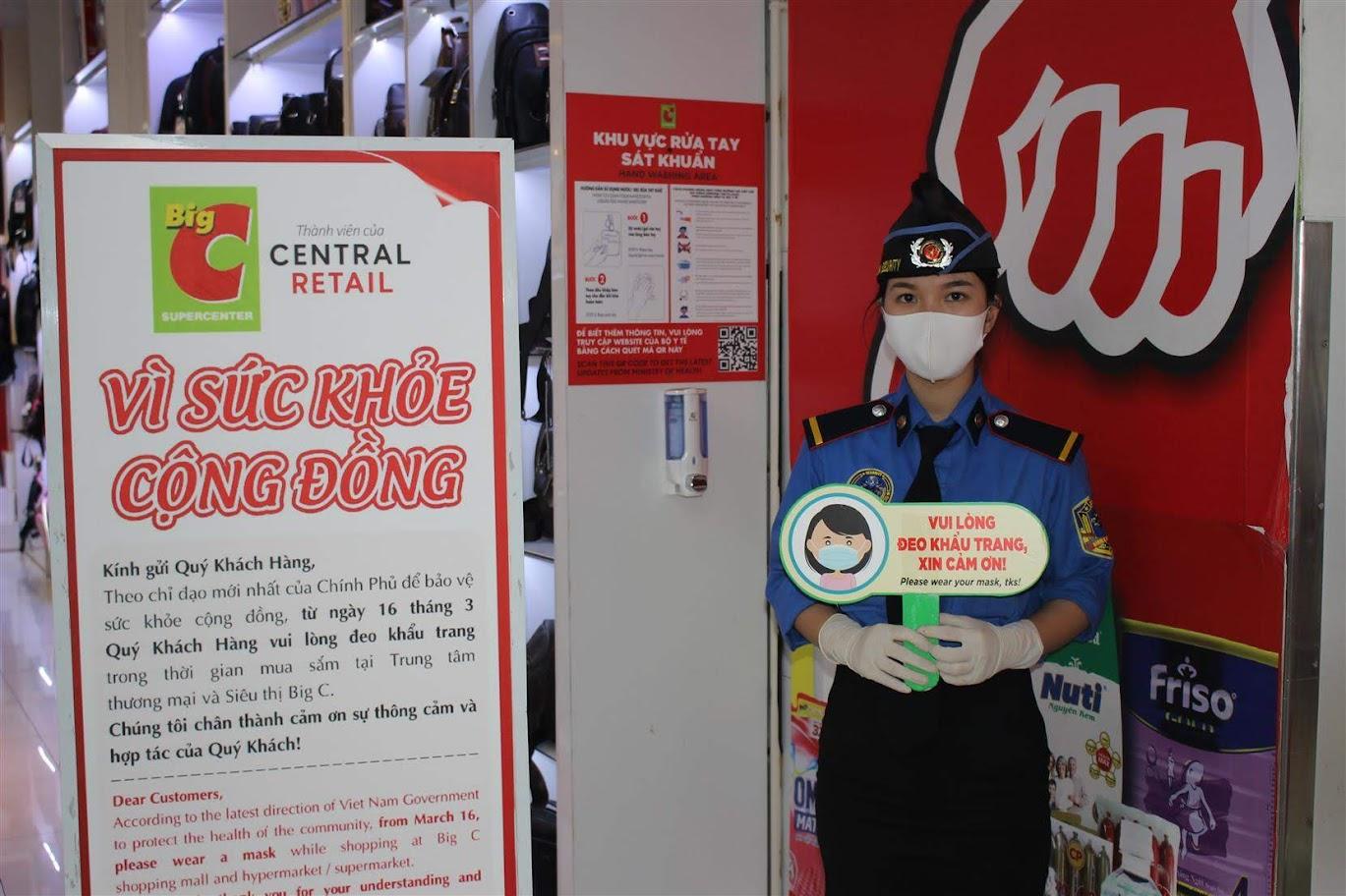 """Ngay lối vào cổng siêu thị Big C Vinh đã có bảng dựng với nội dung """"Từ ngày 16 tháng 3, quý khách vui lòng đeo khẩu trang trong thời gian mua sắm tại trung tâm thương mại và siêu thị Big C"""" bằng cả tiếng Việt và tiếng Anh."""