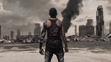 A man with a bionic arm stands with his back to the camera facing a dystopian, dark cityscape.