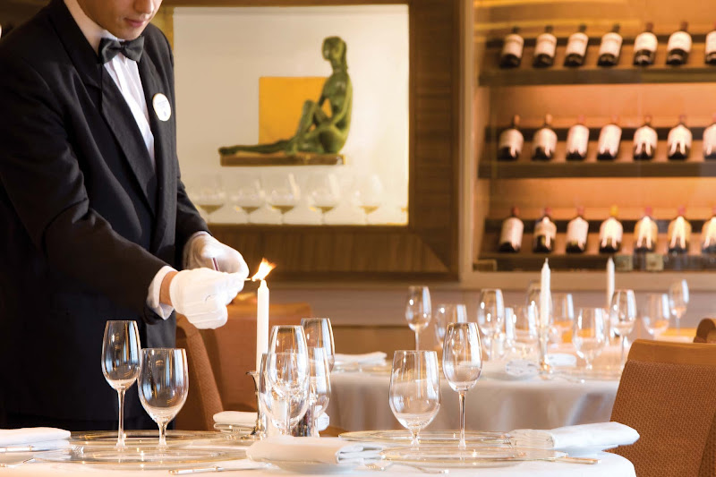 A server prepares a table setting at Le Champagne, the only Relais & Châteaux restaurant at sea, on five Silversea ships.