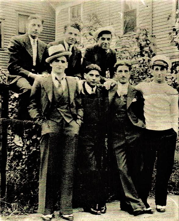 A vintage photo of a group of people posing for the camera  Description generated with very high confidence