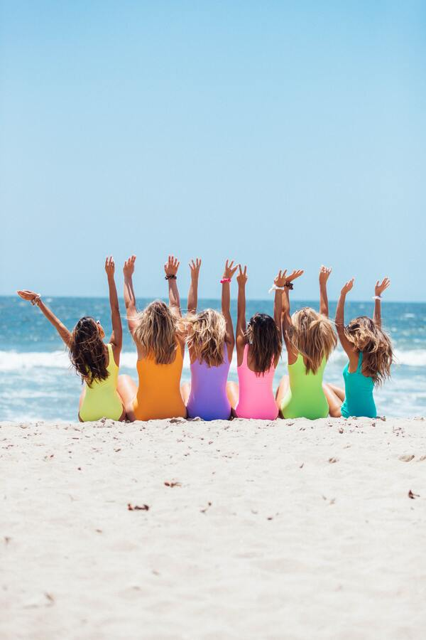 grupo de amigas na praia, de costas para a camera, com os braços levantados