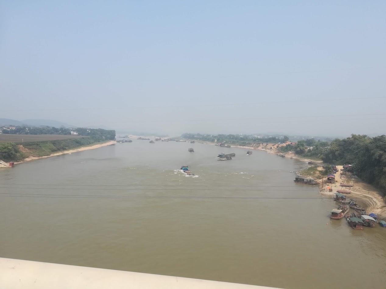 Utsikt fra en bro over Den Røde Elv litt nord for Hanoi. Mye båttrafikk på elven her.