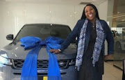 Cheryl Modise poses with her brand new Range Rover Evoque.